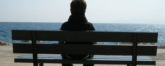 Junge sitzt auf einer Bank